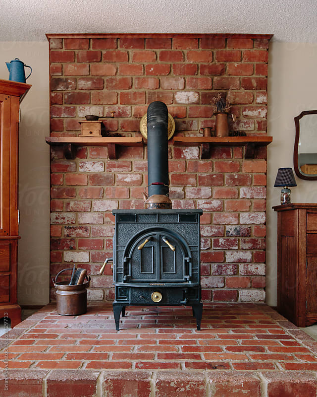 old wood stove on brick hearth by Brian Powell for Stocksy United