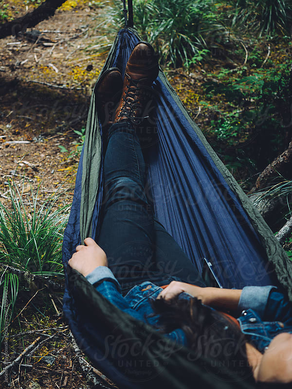 Young asian woman in leather boots lounging in hammock by Jeremy Pawlowski for Stocksy United