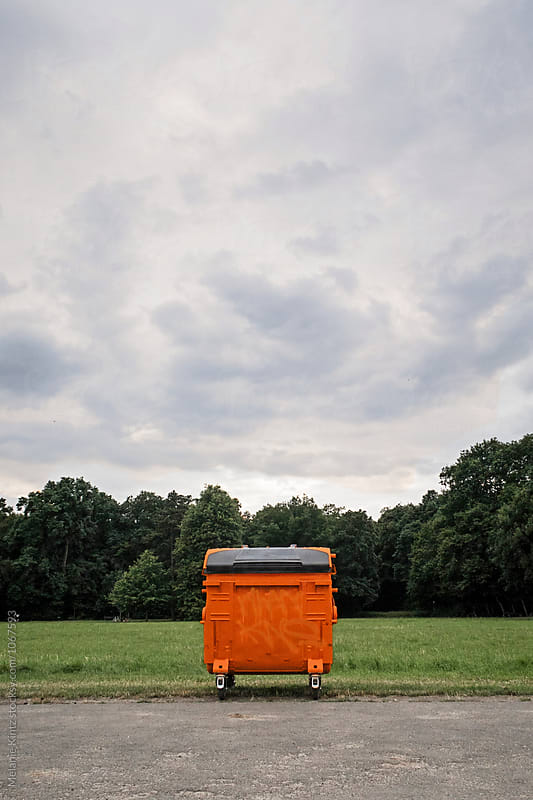 Bright Orange dumpster in a park by Melanie Kintz for Stocksy United