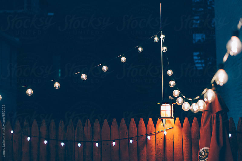 Patio lights at a restaurant just after dusk. by James Jackson for Stocksy United
