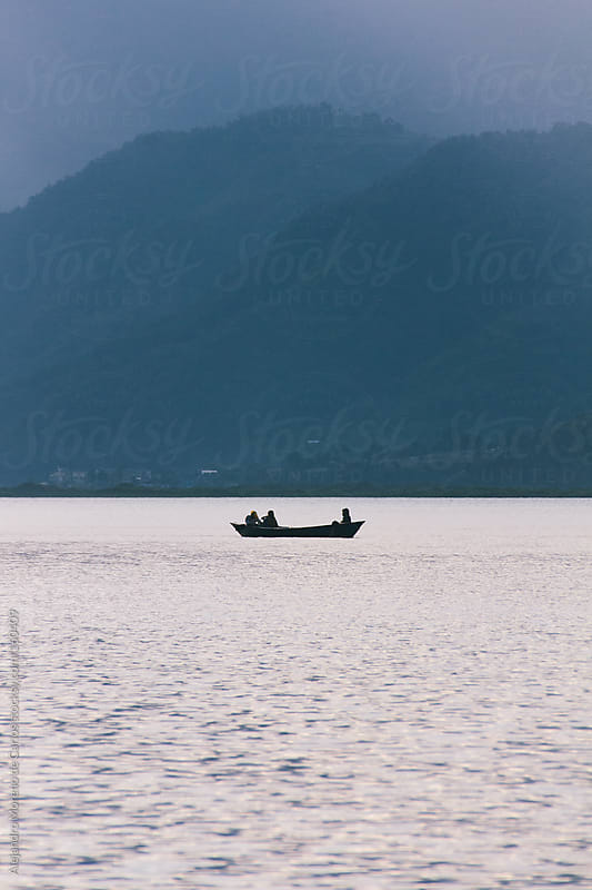 Boat on a lake with mountains. Canoe silhouette. Pokhara, Nepal by Alejandro Moreno de Carlos for Stocksy United