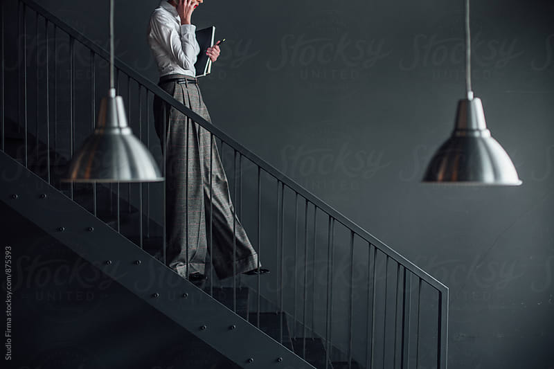 Businesswoman Walking Down the Stairs by Studio Firma for Stocksy United