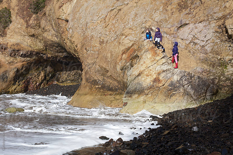 Four kids on a rock wall on the Oregon Coast at high tide by Carleton Photography for Stocksy United
