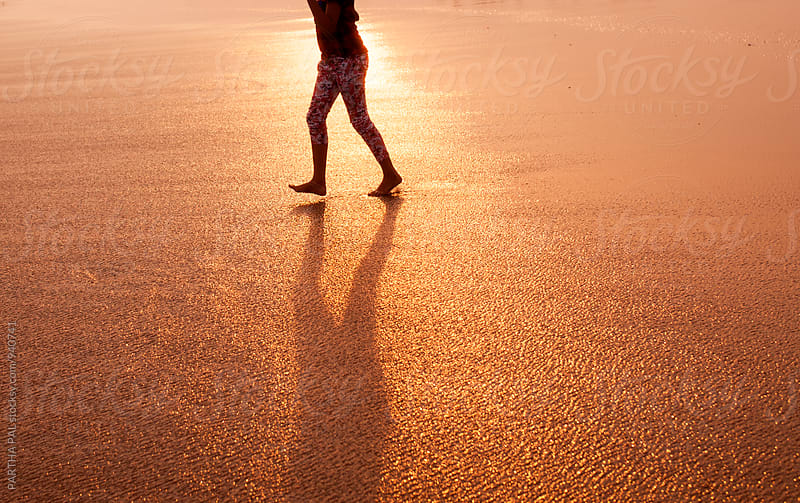 A girl walking on the beach with long shadow by PARTHA PAL for Stocksy United