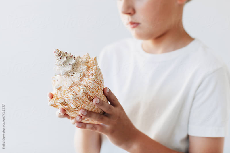 child holding a conch shell  by Kelly Knox for Stocksy United