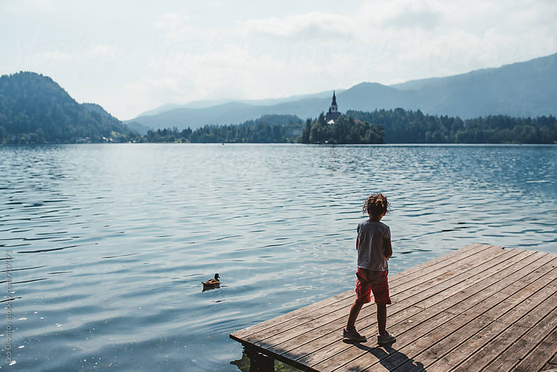 Girl standing on a pier on Lake Bled. by Lea Csontos for Stocksy United