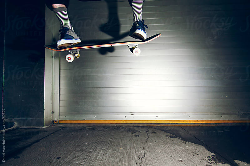 high jump with a skateboard on the sidewalk by Denni Van Huis for Stocksy United
