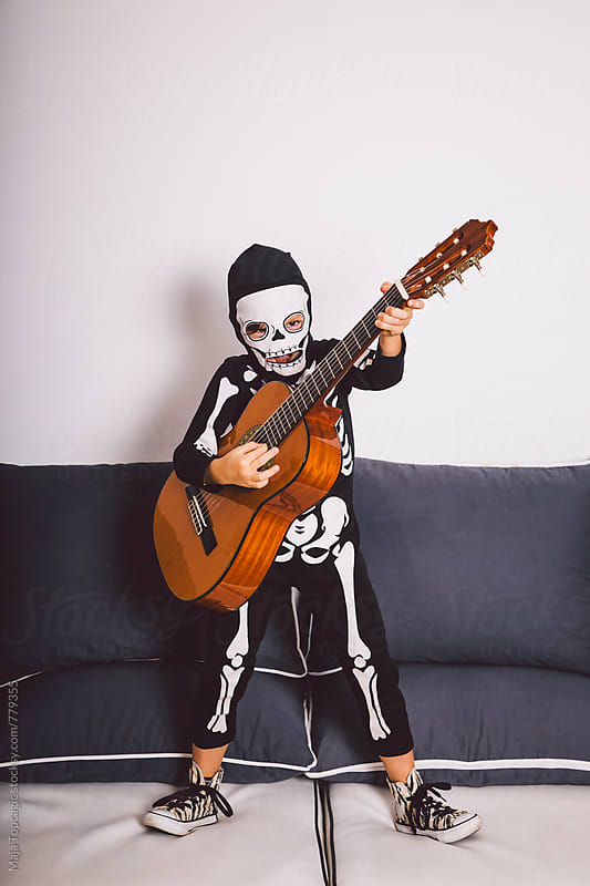 Little boy in a skeleton costume playing a guitar by Maja Topcagic for Stocksy United