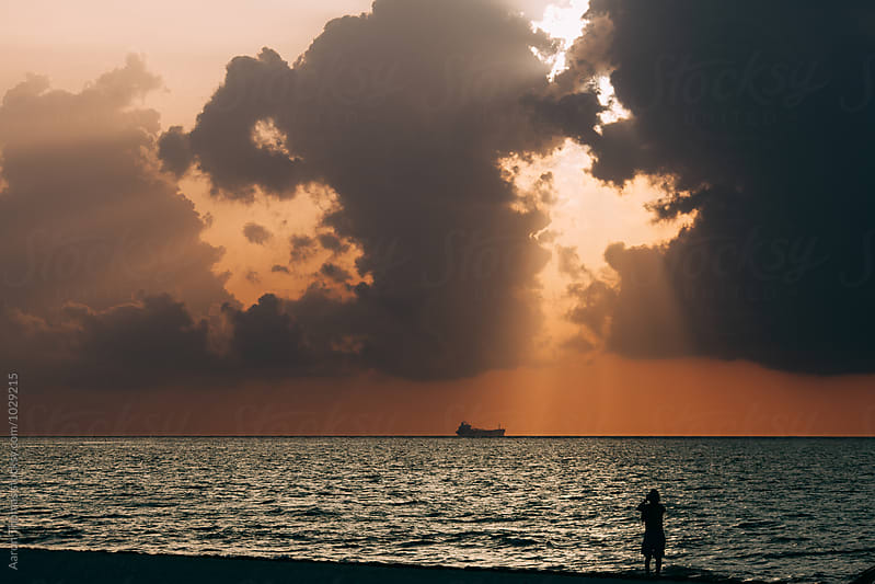 Onlooker watching sunrise in Playa del Carmen by Aaron Thomas for Stocksy United