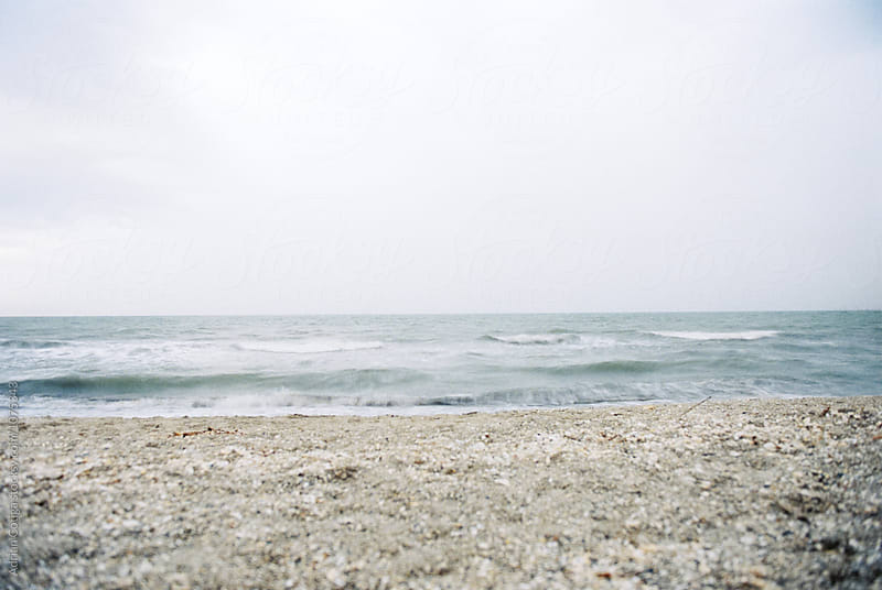 Beach in the summer on a cloudy day  by Adrian Cotiga for Stocksy United