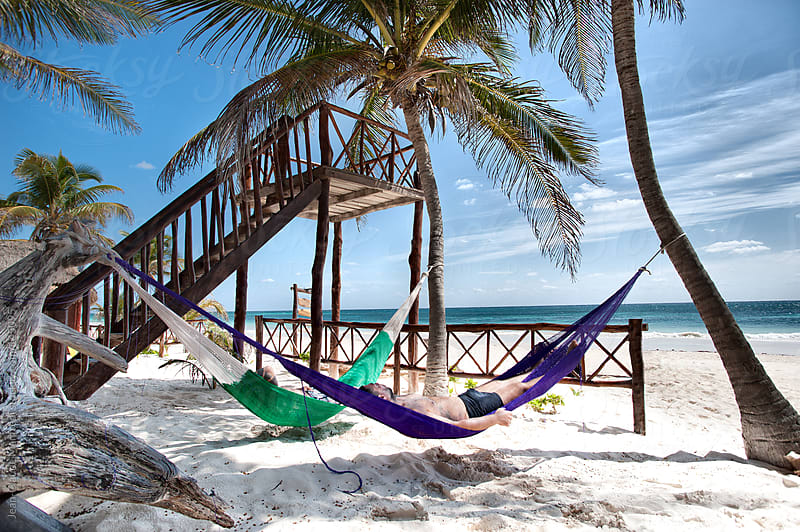 Guys have relax in the hammock on a Caribbean beach by Jean-Claude Manfredi for Stocksy United