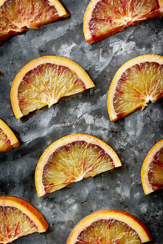 Slices of blood oranges on a metal surface by James Ross for Stocksy United