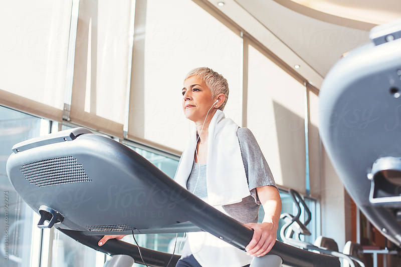 Woman Listening to Music While Walking on a Treadmill by Lumina for Stocksy United