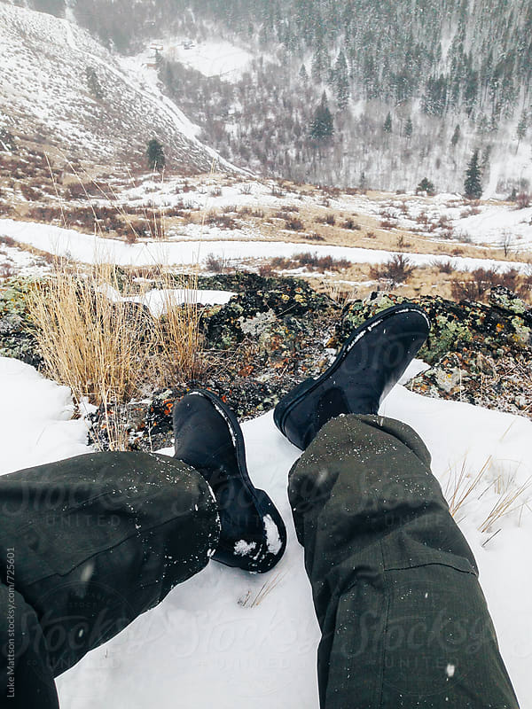 Man In Green Snow Pants And Black Boots Sits On Top Of Hill Covered In Snow by Luke Mattson for Stocksy United