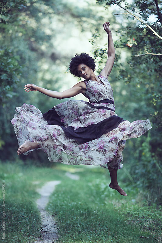 Black woman with dress jumping in forest by Robert Kohlhuber for Stocksy United