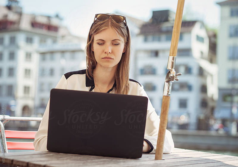 Young Female Professional Working on Her Laptop in a Restaurant by Julien L. Balmer for Stocksy United