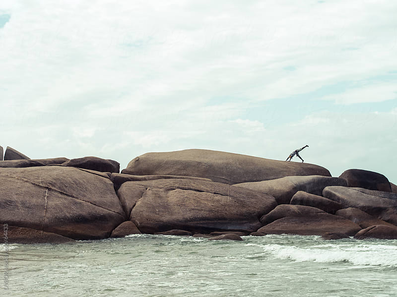 Man exercising on boulders by the beach by DV8OR for Stocksy United
