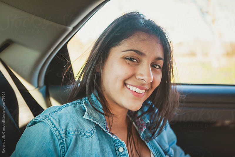 Cute teen girl enjoying car ride in backseat by Rob and Julia Campbell for Stocksy United