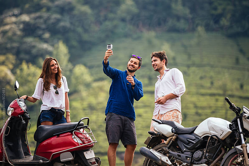 Three young friends standing next to motorbikes in front of a hill of tea plantations taking a selfie picture by Alejandro Moreno de Carlos for Stocksy United