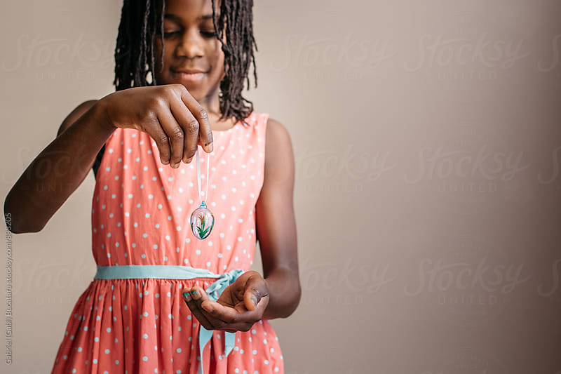 Black girl holding an Easter egg decoration by Gabriel (Gabi) Bucataru for Stocksy United