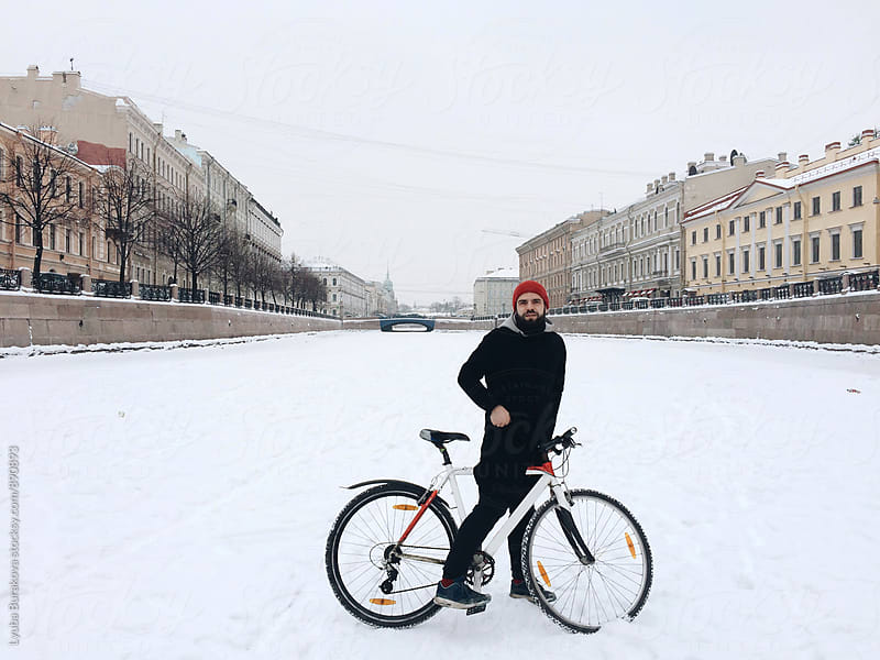 Man with bicycle on a riverbed by Lyuba Burakova for Stocksy United