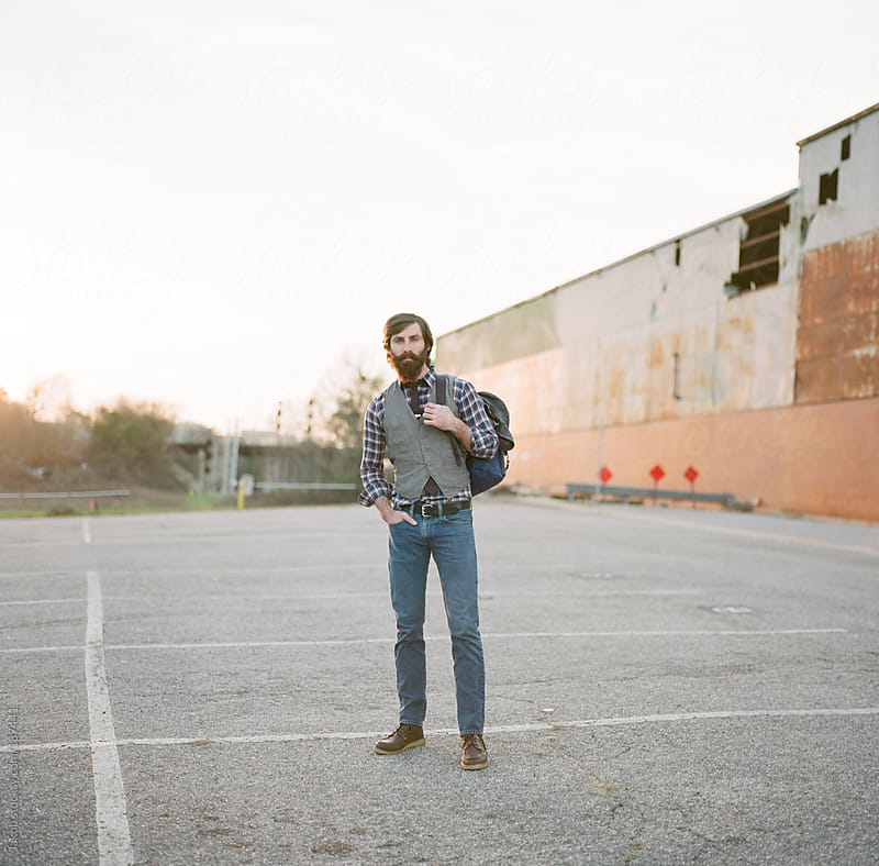 Portrait of a stylish and bearded man in a parking lot by Jakob for Stocksy United