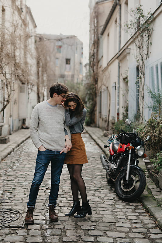 Cute couple holding each other in streets of paris by Phil Chester Photography for Stocksy United