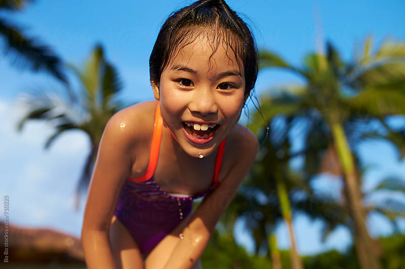 Close up of lovely little asian girl smile at camera by swimming pool by Bo Bo for Stocksy United