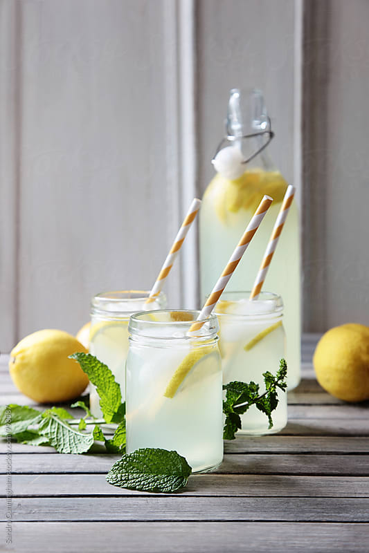 Glasses of homemade lemonade with mint on table by Sandra Cunningham for Stocksy United