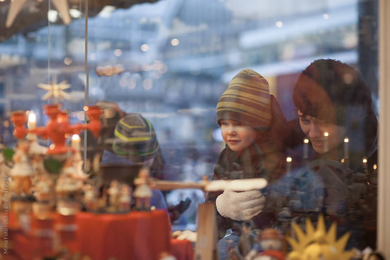 Mother and son looking through window at wooden toys by Mima Foto for Stocksy United