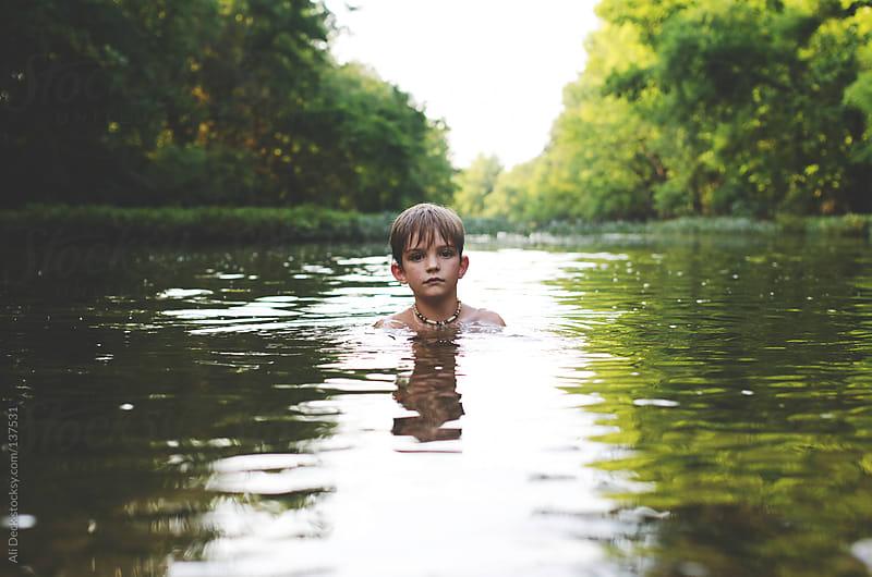 Boy in creek water by Ali Deck for Stocksy United