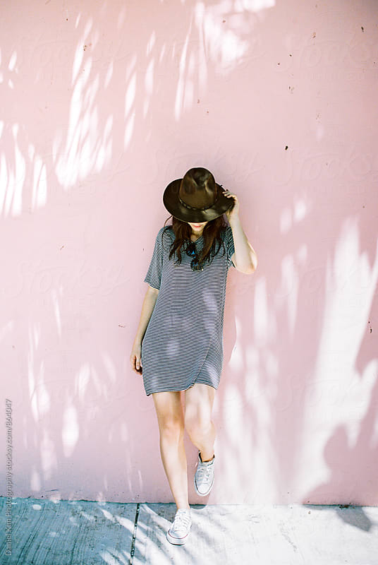 Woman leaning on pink wall by Daniel Kim Photography for Stocksy United