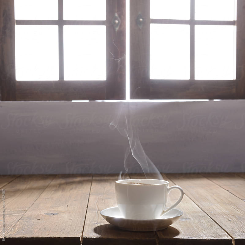 Steaming cup of coffee on the table by RG&B Images for Stocksy United