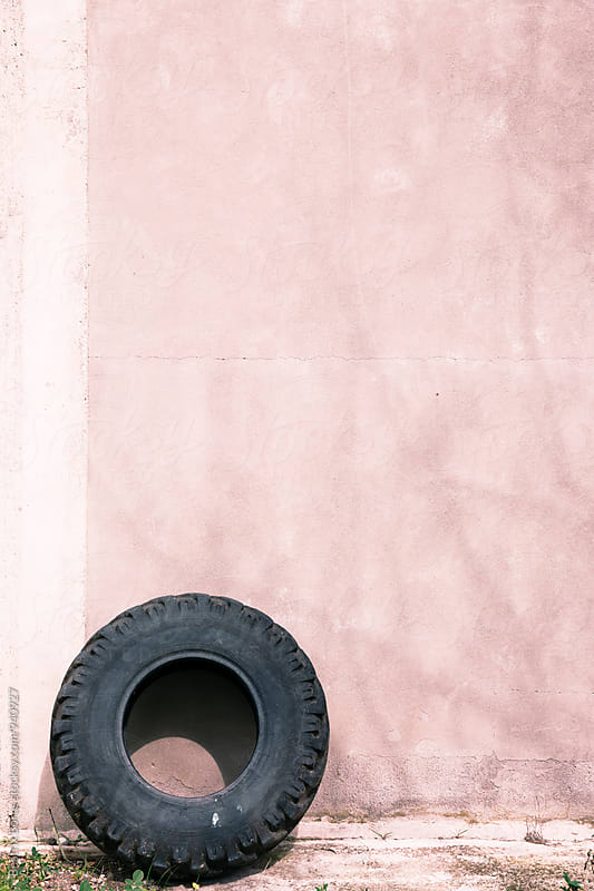 Tyre against a pastel pink wall with light shadow of a tree by Beatrix Boros for Stocksy United