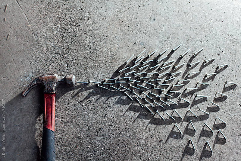 A hammer spewing nails in a concept idea. by J Danielle Wehunt for Stocksy United