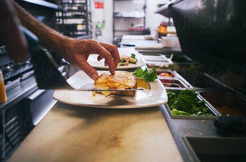 Kitchen: Putting Grilled Cheese On Plate by Sean Locke for Stocksy United