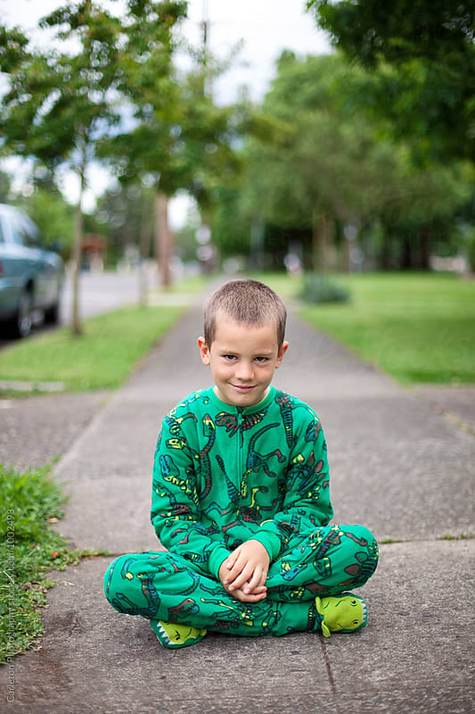 Boy in pajamas sitting cross legged on a sidewalk by Carleton Photography for Stocksy United