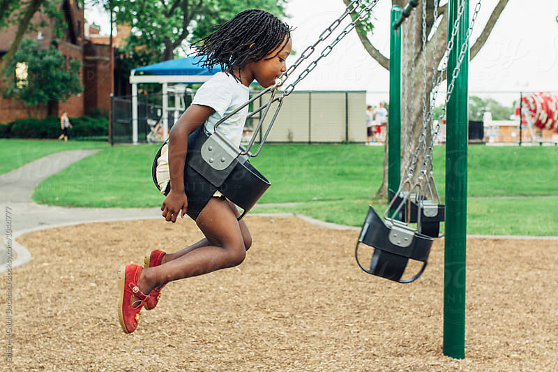 Black girl swinging at a playground by Gabriel (Gabi) Bucataru for Stocksy United