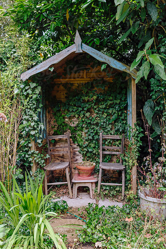 Small garden shelter with two chairs in a rural garden by for Small garden shelter