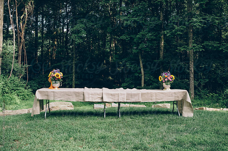 Tables decorated with bouquets and tablecloth for a celebration party by Trent Lanz for Stocksy United