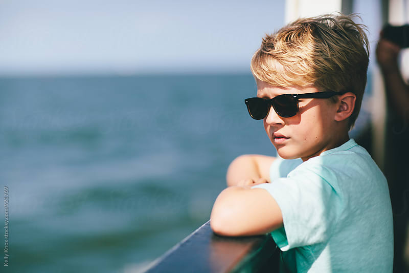 portrait of a boy looking at the ocean from a boat by Kelly Knox for Stocksy United