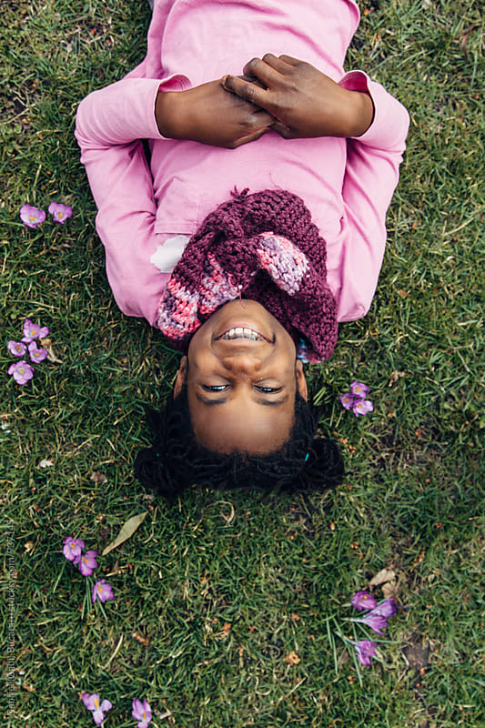 Smiling upside down black girl laying on grass with crocus flowers by Gabriel (Gabi) Bucataru for Stocksy United