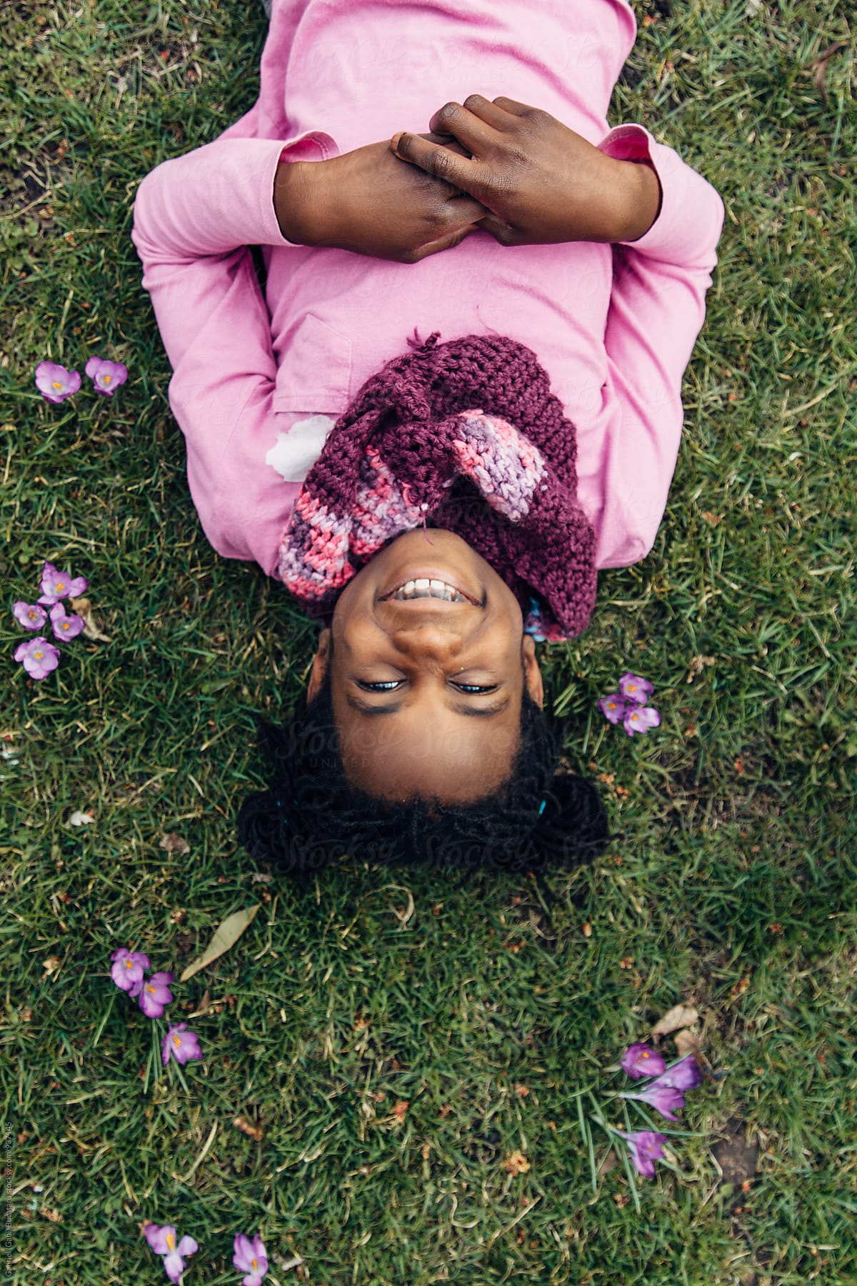 Smiling Upside Down Black Girl Laying On Grass With Crocus Flowers