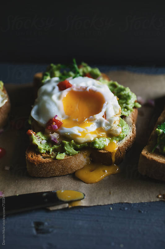 Avocado toast with soft fried egg. by Darren Muir for Stocksy United