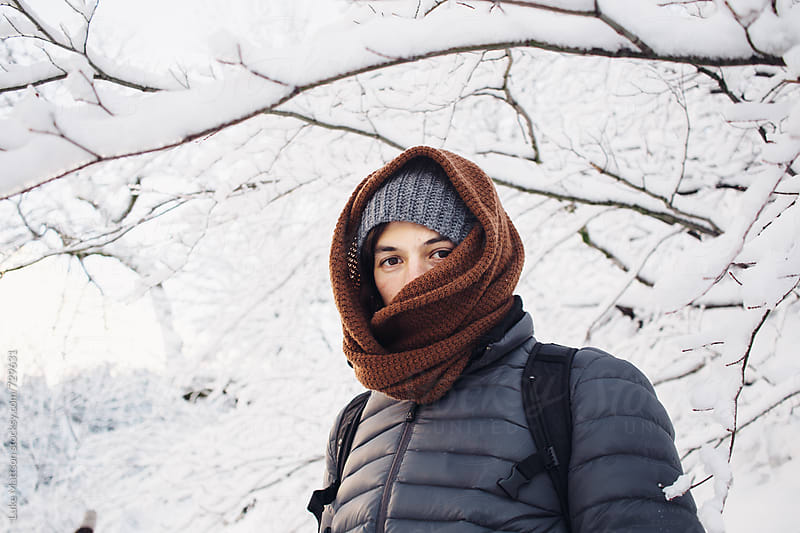 Young Man Wrapped In Scarf Standing Under Snow Covered Branches During Winter by Luke Mattson for Stocksy United