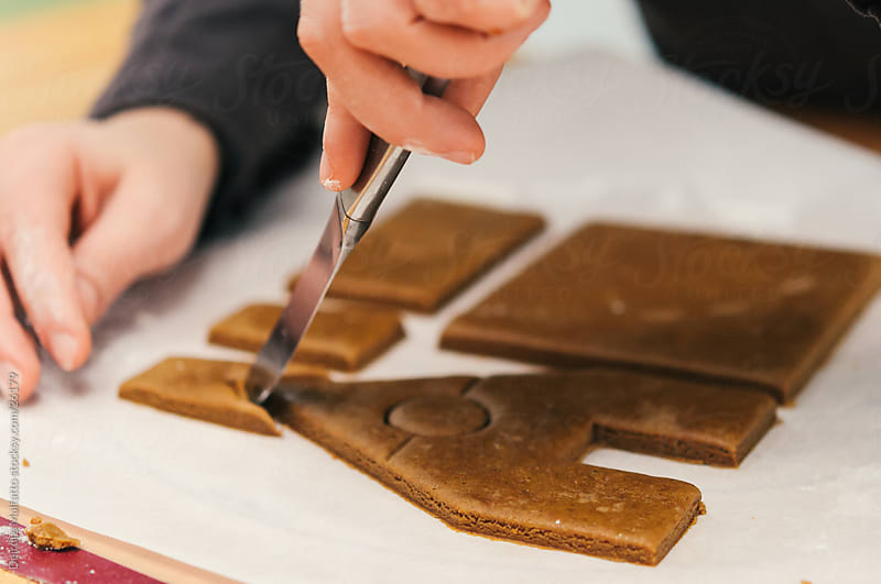 Hands cutting pieces for a gingerbread house by Deirdre Malfatto for Stocksy United