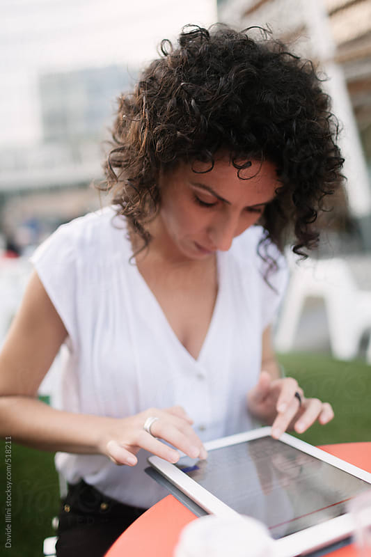 Businesswoman working with digital tablet in a coffee by Davide Illini for Stocksy United
