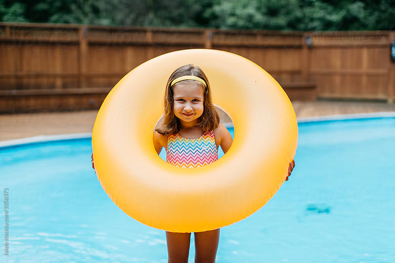 Cute young girl standing by a pool holding an intertube by Jakob for Stocksy United