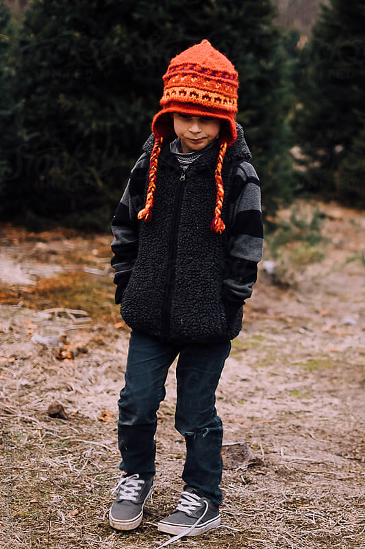 child with orange hat at christmas tree farm by Léa Jones for Stocksy United