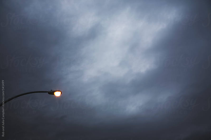 Street Light shining with moody skies by Rob and Julia Campbell for Stocksy United